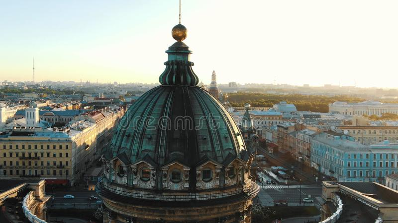 Tremendous green dome lit by sunset against endless city stock photos