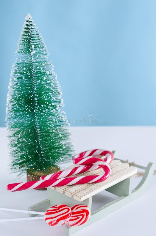 Trenó de madeira com doces e árvore de Natal Plano vertical foto de stock