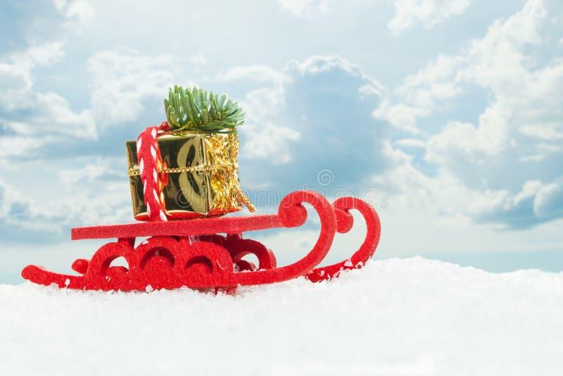 Trenó de Santa do Natal com árvore do Xmas e presente do ouro no fundo branco da neve contra o céu com nuvens Composi??o do Natal foto de stock royalty free