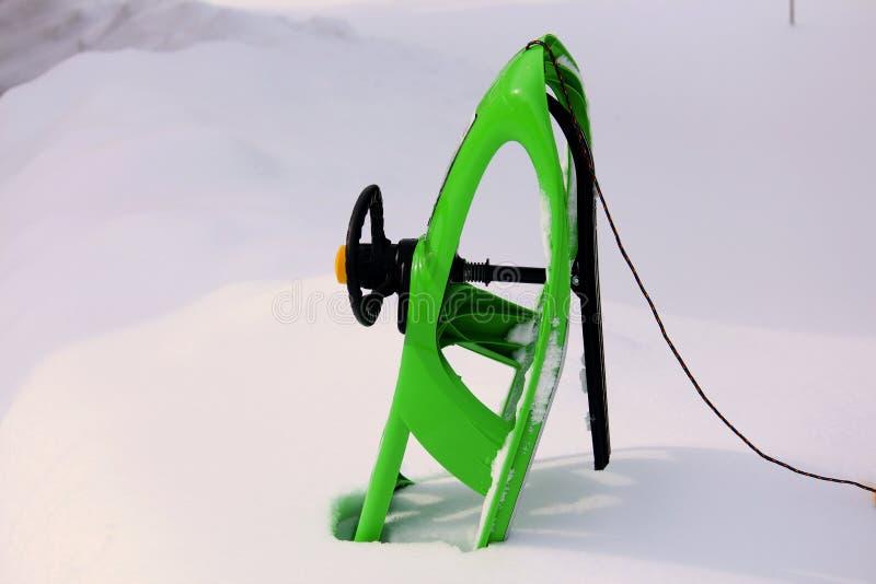 trenó verde com a neve isolada no fundo branco foto de stock