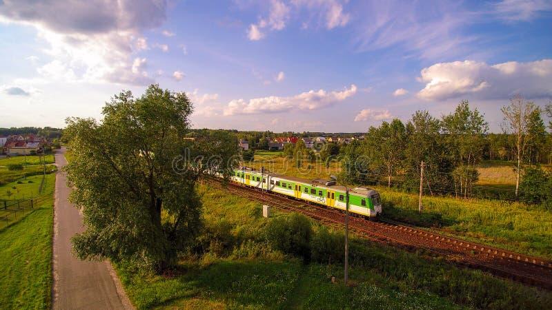 Tren blanco y verde que pasa a través de pequeño pueblo durante la tarde soleada fotos de archivo libres de regalías