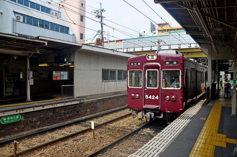 Tren clásico rojo de la línea de Hankyu Kyoto que corre del statio de Kyoto imagenes de archivo