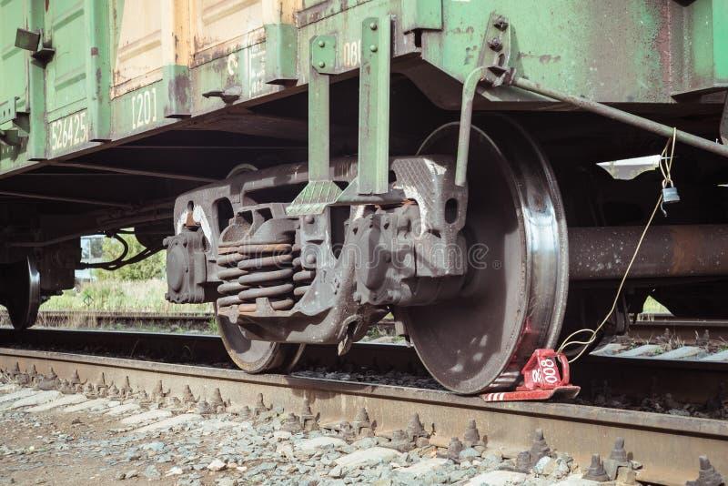 Tren de carga con una cuña de la rueda en la plataforma imagen de archivo