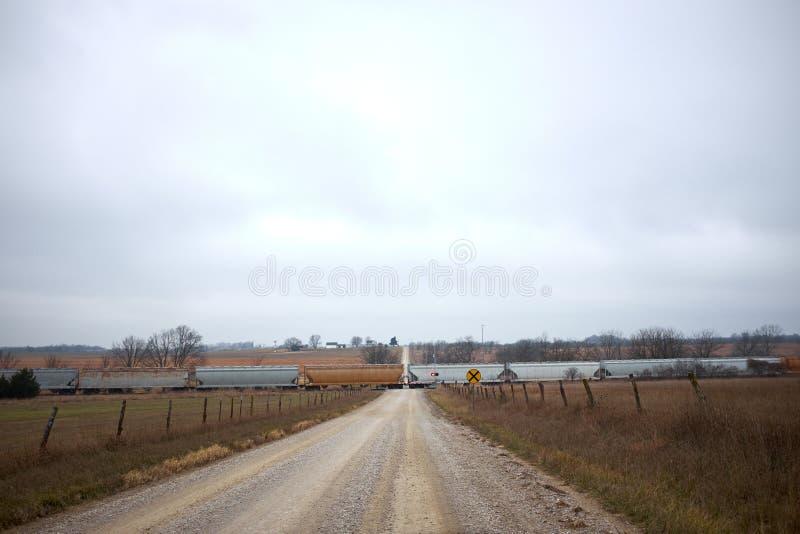 Tren de carga largo que cruza un camino rural remoto fotografía de archivo