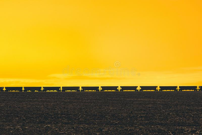 Tren de carga que pasa encendido en el horizonte del campo en el campo americano Luz de la puesta del sol y el cielo tempestuoso imagen de archivo
