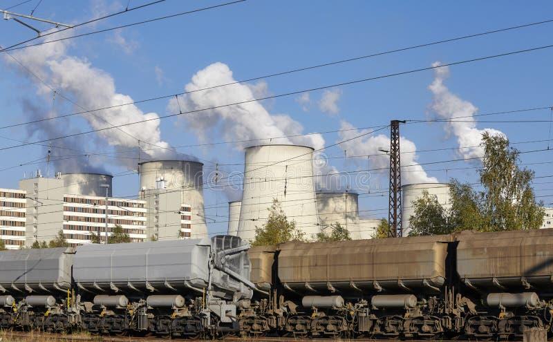 Tren de carga y una central el?ctrica con las chimeneas que fuman fotografía de archivo libre de regalías