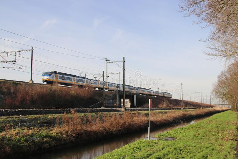 Tren de cercanías local blanco, azul y amarillo en vía en Zwijndrecht los Países Bajos fotos de archivo