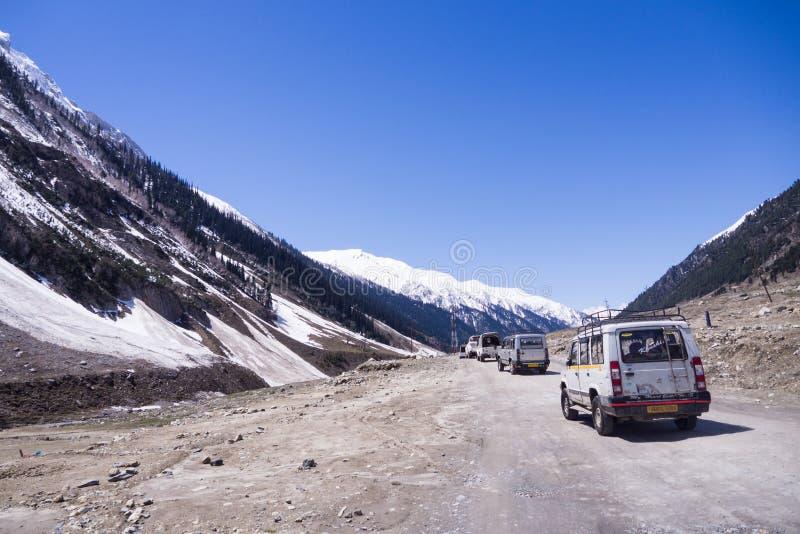 Tren de coches en el camino de la aventura entre la montaña de la nieve imágenes de archivo libres de regalías