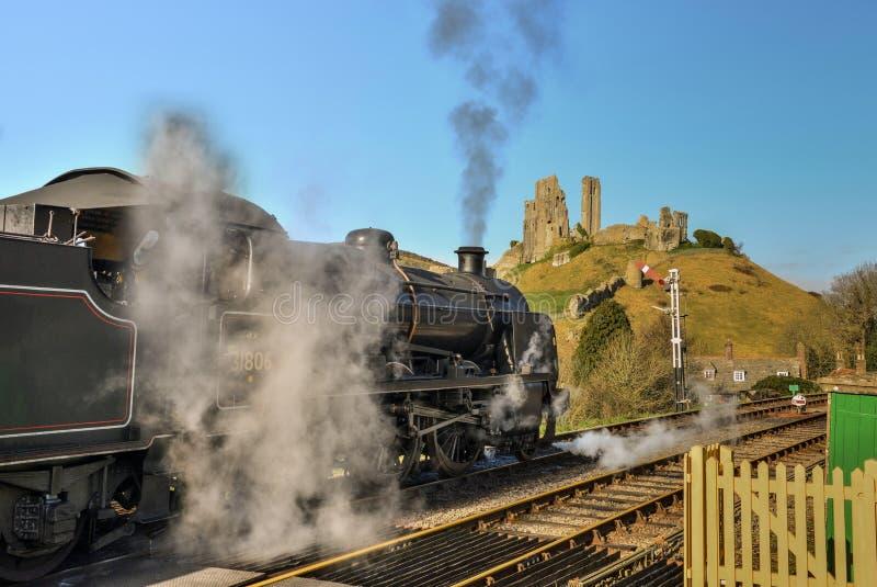 Tren de la corriente a través de la estación de tren del pueblo de Corfe imágenes de archivo libres de regalías