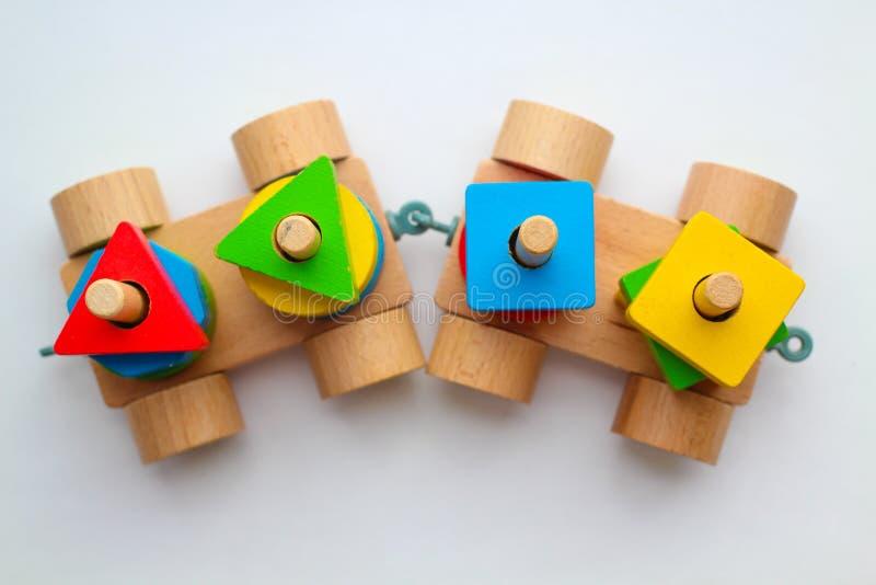 Tren de madera de la visión superior en el fondo blanco Los detalles coloridos del juguete dibujan la atención del bebé fotografía de archivo