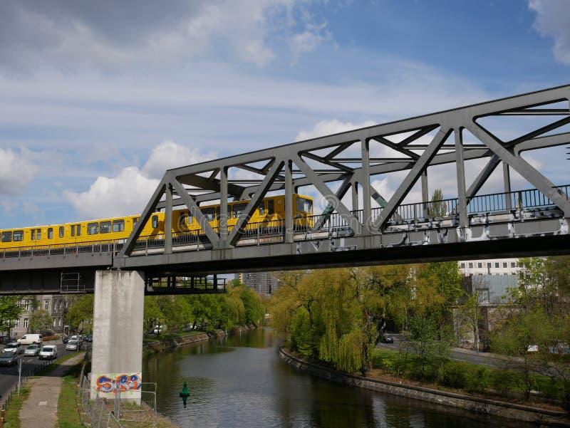 Tren de pasajeros amarillo brillante que cruza un puente foto de archivo libre de regalías