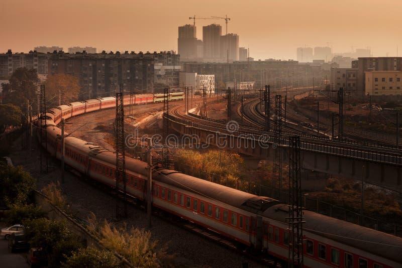 Tren de pasajeros en la puesta del sol imagen de archivo