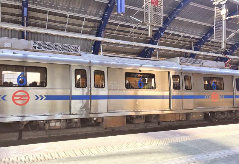 Tren del metro de Delhi en una estación de metro menos apretada en Nueva Deli en el tiempo del mediodía imagen de archivo