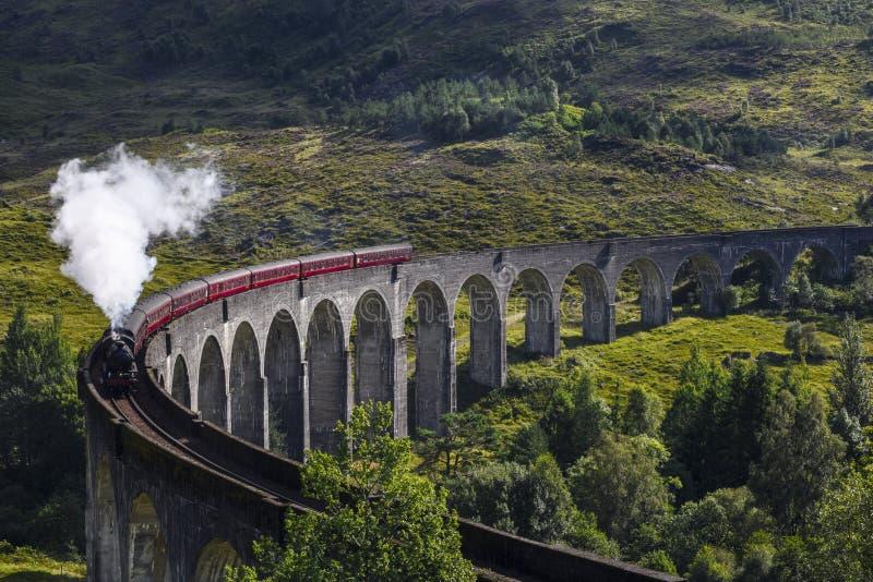Tren del vapor de Jacobite en el viaducto de Glenfinnan en el lago Shiel, Mallaig, montañas, Escocia fotografía de archivo libre de regalías