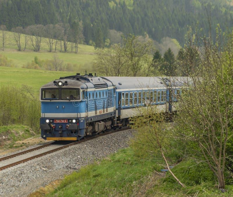 Tren diesel azul con el coche de pasajeros en las montañas de Jeseniky imágenes de archivo libres de regalías