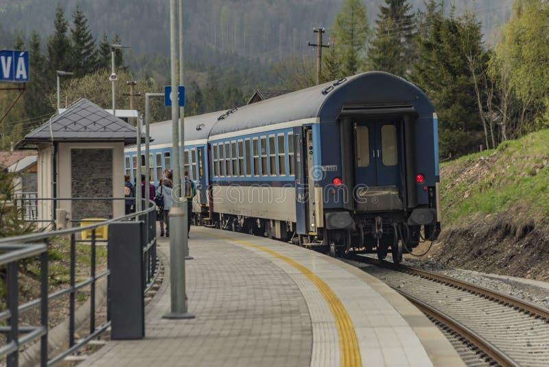 Tren diesel azul con el coche de pasajeros en las monta?as de Jeseniky imagen de archivo