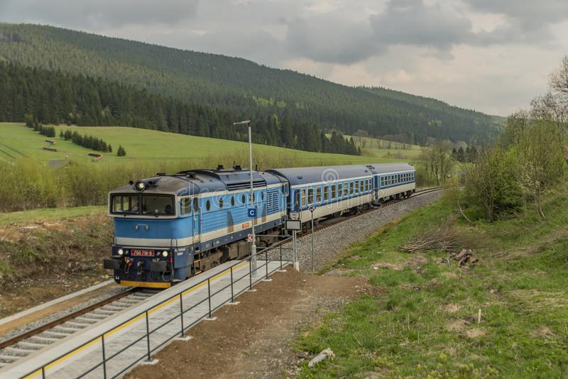 Tren diesel azul con el coche de pasajeros en las monta?as de Jeseniky foto de archivo