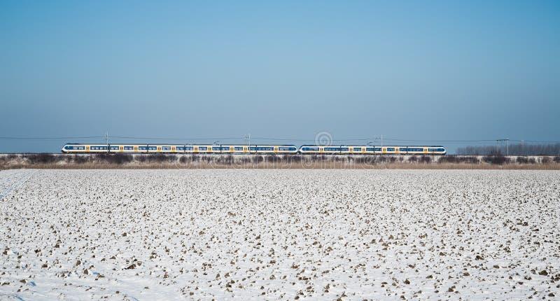 Tren en paisaje holandés de las tierras de labrantío del invierno fotografía de archivo libre de regalías