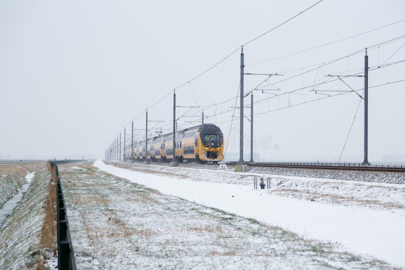 Tren en paisaje rural holandés del invierno fotos de archivo