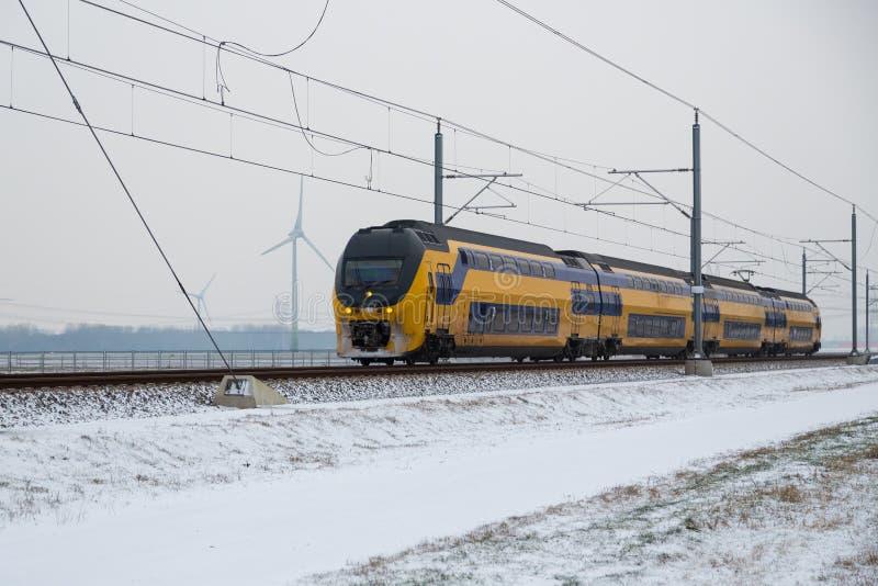 Tren en paisaje rural holandés del invierno imagen de archivo libre de regalías