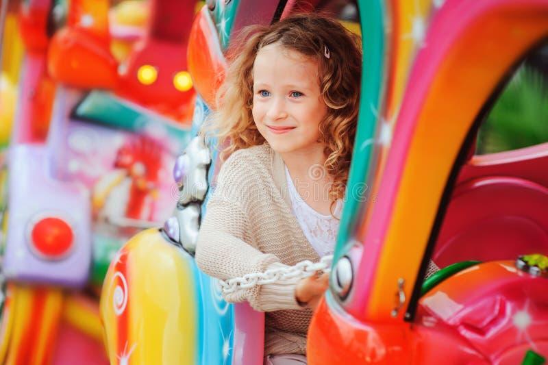 Tren feliz del montar a caballo de la muchacha del niño en funfair el vacaciones de verano foto de archivo libre de regalías