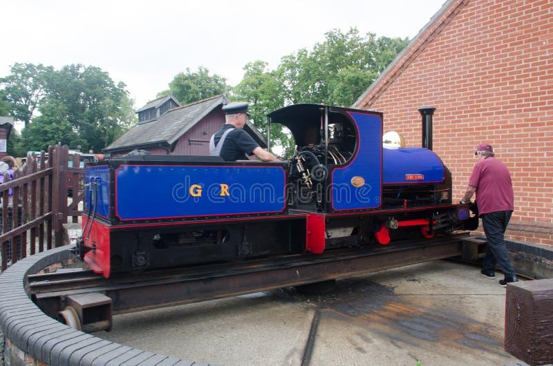 Tren ferroviario azul del indicador estrecho que es empujado en placa giratoria imágenes de archivo libres de regalías