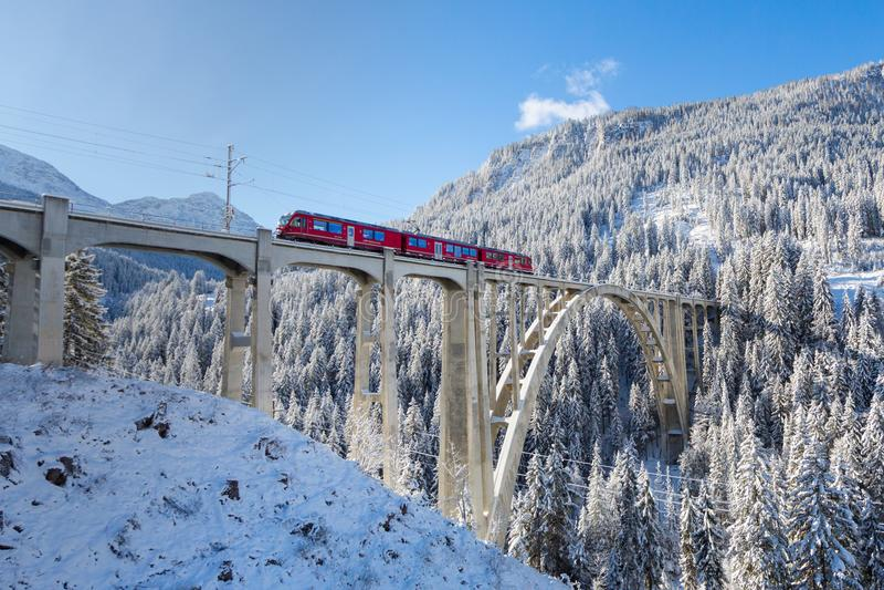 Tren ferroviario rojo de Rhaetian en el viaducto Langwies, sol, invierno foto de archivo libre de regalías