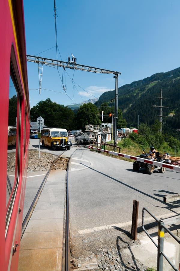 Tren que cruza una calle con las barreras abajo de y el tráfico que espera en ambos lados foto de archivo