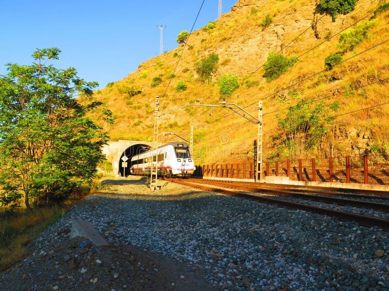 Tren que emerge del túnel en vía eléctrica fotografía de archivo libre de regalías