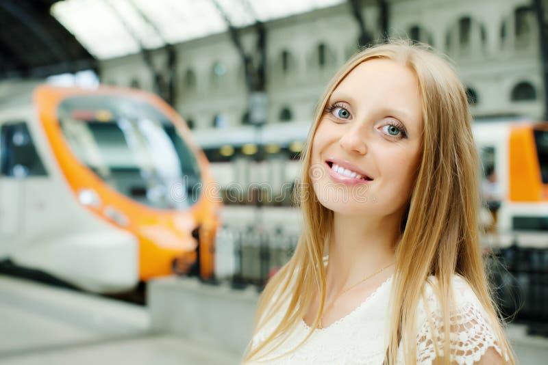 Tren que espera de la mujer en la estación foto de archivo