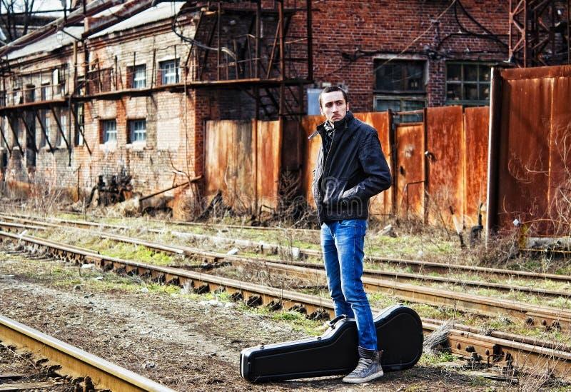 Tren que espera del hombre joven para entre el ru industrial fotografía de archivo