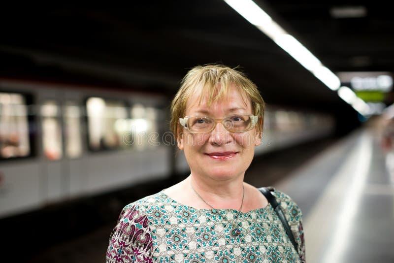 Tren que espera del viajero mayor de la mujer fotografía de archivo