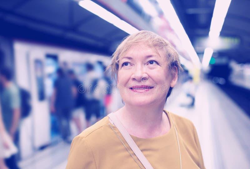 Tren que espera del viajero mayor de la mujer imagenes de archivo