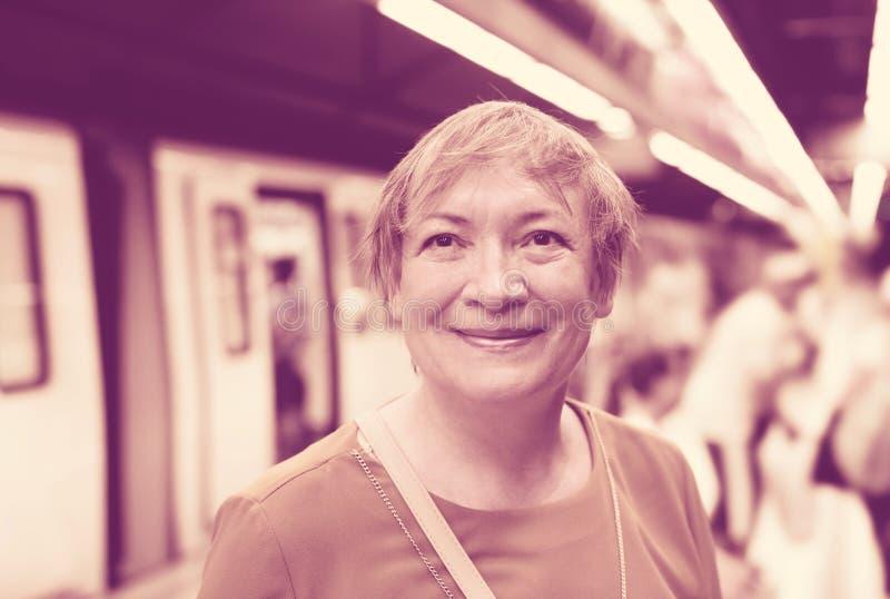 Tren que espera del viajero mayor de la mujer fotos de archivo
