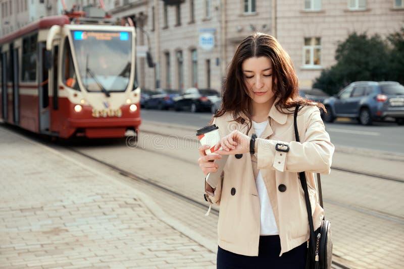 Tren que espera o tranvía de la mujer bastante joven para como llegada, comprobando el tiempo en smartwatch, taza de café para ll imagen de archivo libre de regalías
