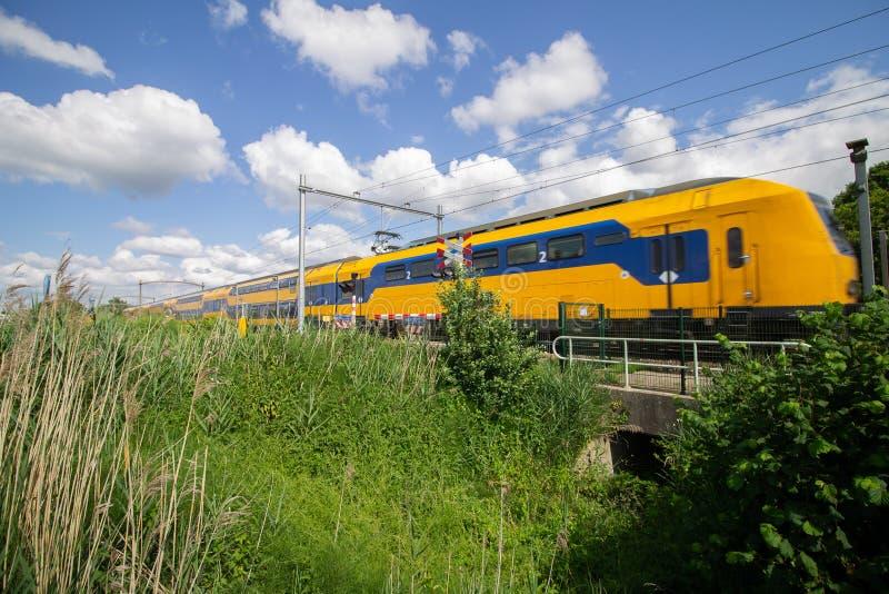 Tren que pasa un paso a nivel en un día soleado con algunas nubes fotografía de archivo