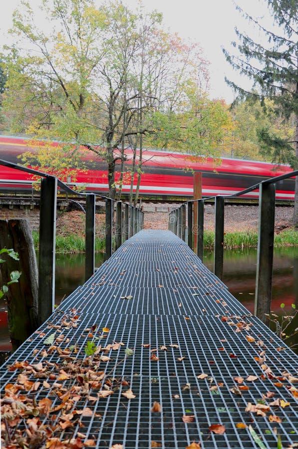 Tren rojo que pasa rápidamente un lago con un puente en Alemania fotografía de archivo