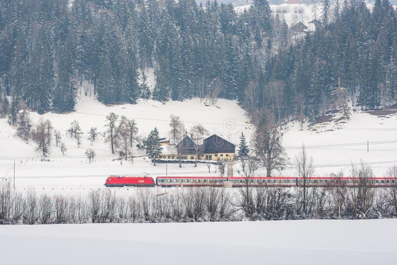 Tren rojo y blanco que pasa los campos nevados en un paisaje esc?nico de la monta?a del invierno, macizo de Dachstein, distrito d imágenes de archivo libres de regalías