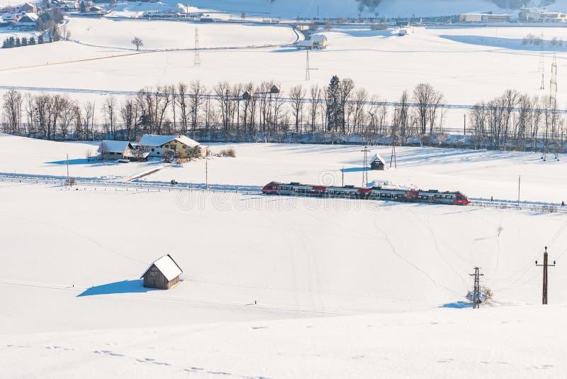 Tren rojo y blanco que pasa los campos nevados en un paisaje esc?nico de la monta?a del invierno, macizo de Dachstein, distrito d fotos de archivo libres de regalías
