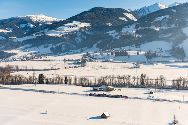 Tren rojo y blanco que pasa los campos nevados en un paisaje esc?nico de la monta?a del invierno, macizo de Dachstein, distrito d foto de archivo