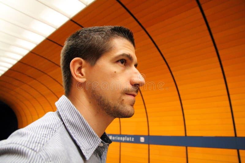 Tren subterráneo que espera ocasional del hombre joven para fotografía de archivo