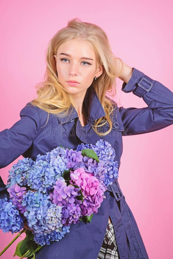 Trench coat fashion trend. Fashionable coat. Must have concept. Clothes and accessory. Woman blonde hair posing coat. With flowers bouquet. Girl fashion model royalty free stock photo