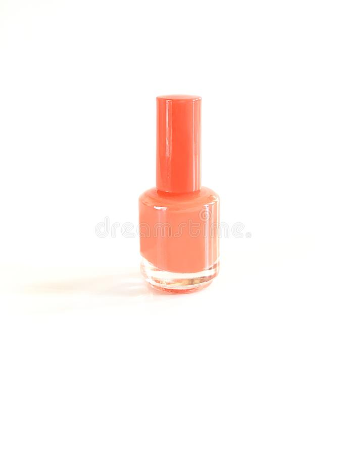 Trend of the actual colors for season 2019 - living coral. Isolated nail bottle on a white background with a place for the stock image