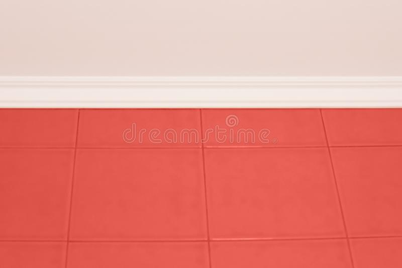 Trend concept color of the year 2019 Living Coral. Trendy laconic elegant bathroom interior with coral-colored wall tiles, stucco on the ceiling and white plinth stock image