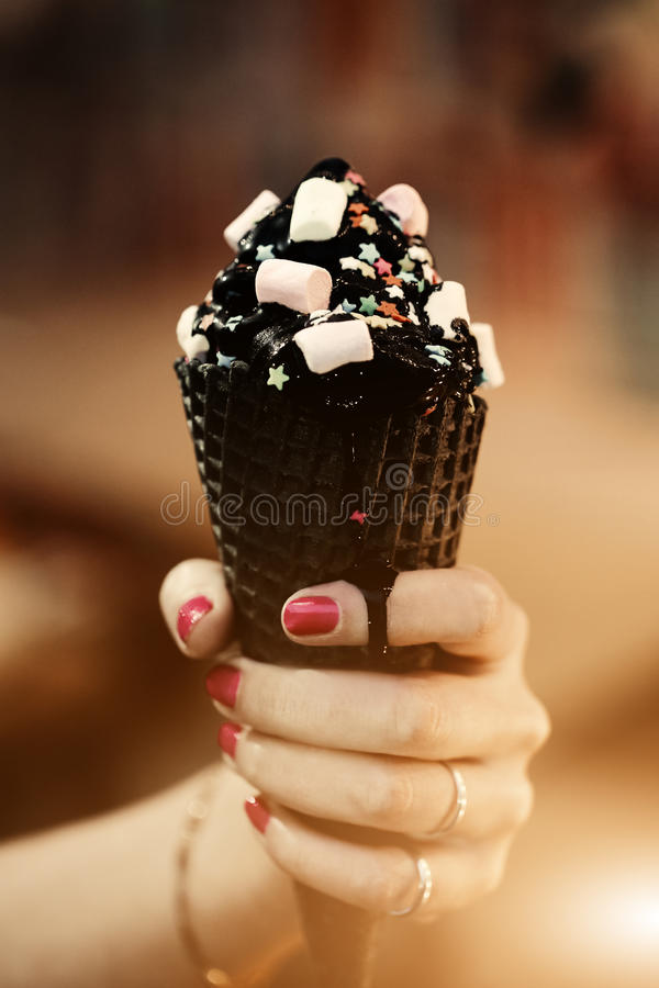 Trend cone of charcoal ice cream with Confetti and food powder, pink and blue fluffy sweet in women`s arm. Blurred bokeh. City background, Sunlight flare for royalty free stock images