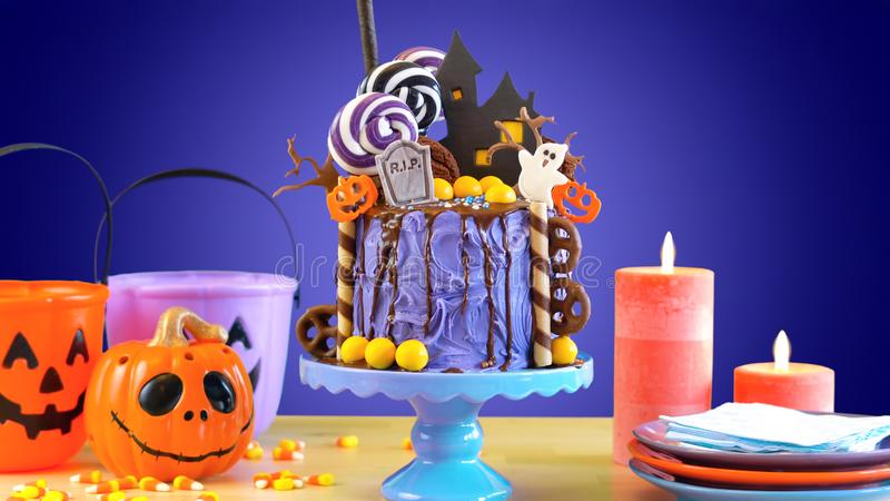 On trend Halloween candyland novelty drip cake in colorful purple party setting. stock images