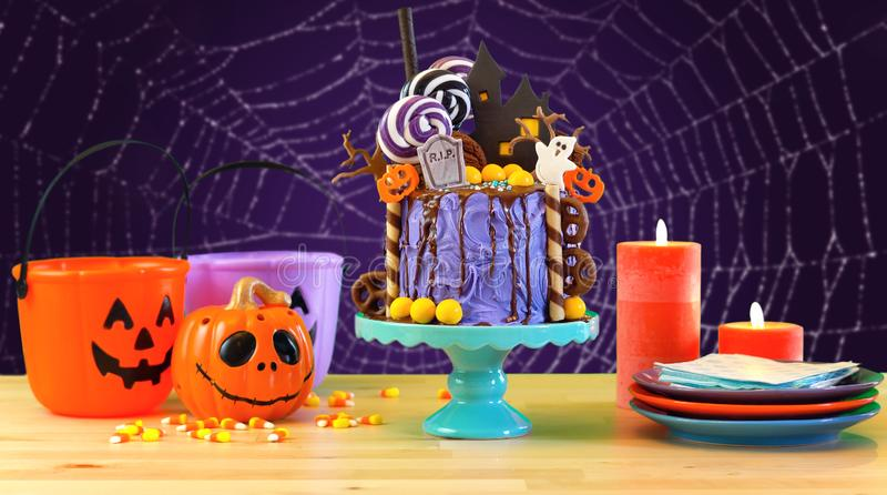 On trend Halloween candyland novelty drip cake in colorful purple party setting. stock photos