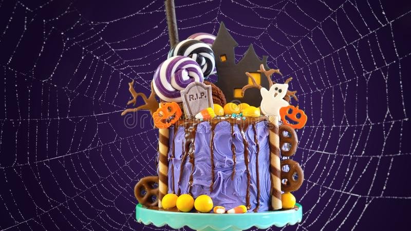 On trend Halloween candyland novelty drip cake in colorful purple party setting. stock photography