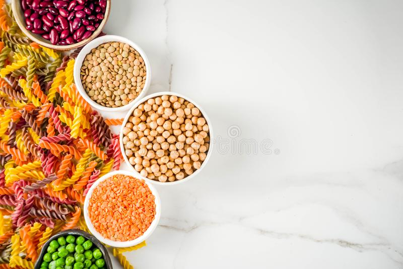 Trend healthy food, vegan diet concept. Multi colored legume pasta with raw beans. Beans, chickpeas, green peas, lentils. Copy. Space top view royalty free stock photography
