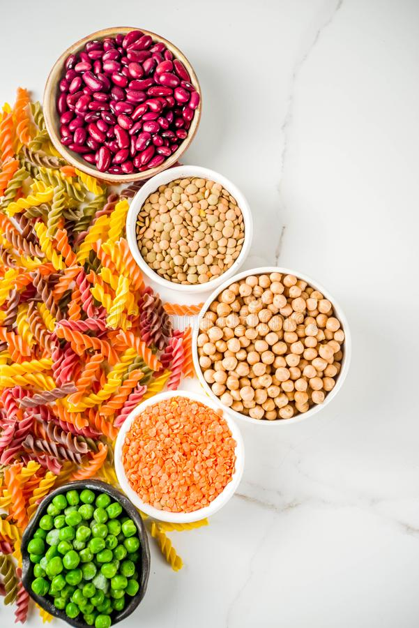 Trend healthy food, vegan diet concept. Multi colored legume pasta with raw beans. Beans, chickpeas, green peas, lentils. Copy. Space top view stock photography